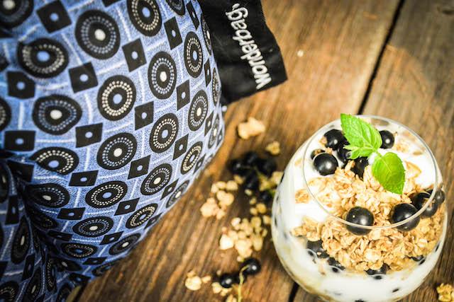 en blå wonderbag med et glass hjemmelaget yoghurt pyntet med økologisk Lykkemat-granola, solbær og mynteblad