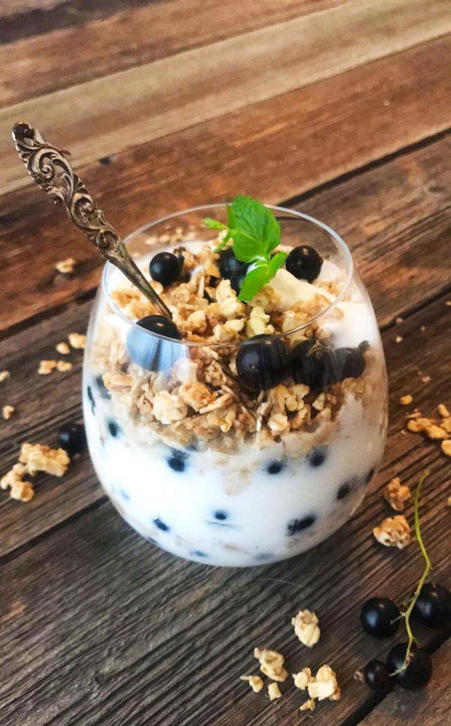 hjemmelgaet yoghurt i et glass med granola, solbær og mynte