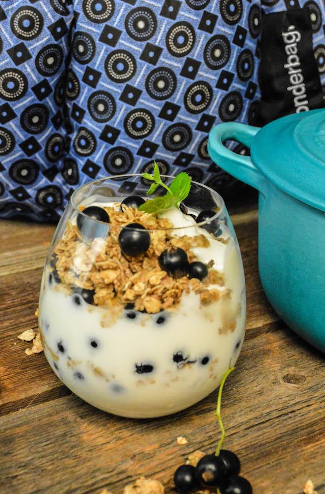 turkis le creusetgryte med en blå wonderbag og et glass hjemmelaget yoghurt pyntet med solbær, granola og mynteblad.